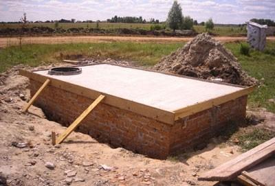 Укладка плиты перекрытия на выгребную яму с люком